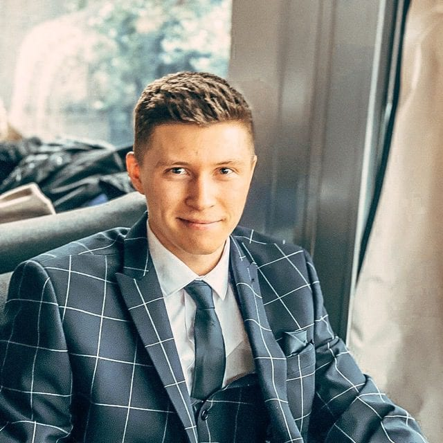 a man sitting in a chair wearing a suit and smiling