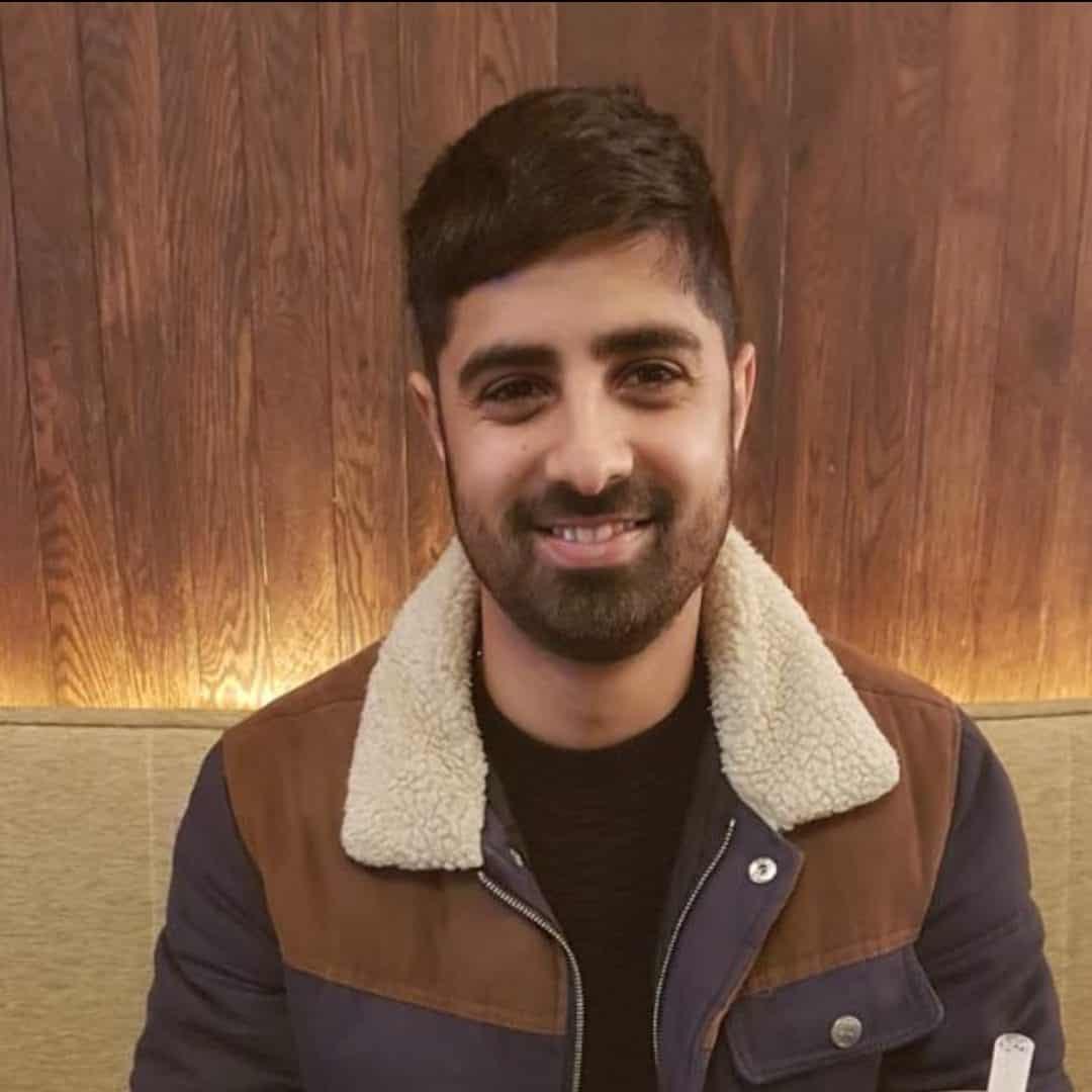 a man smiling wearing a coat