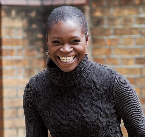 a woman smiling wearing a black jumper