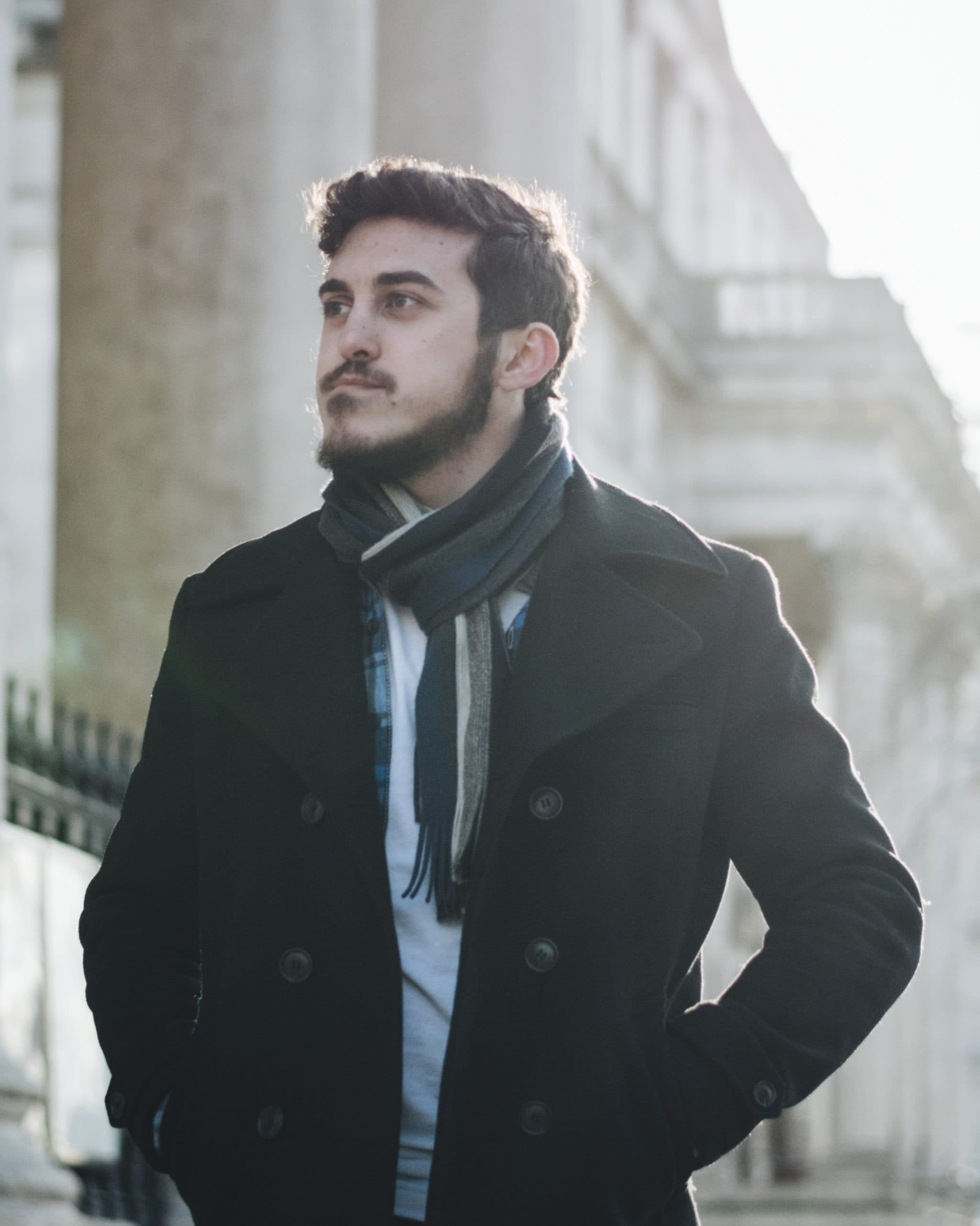 a man with a beard wearing a cost and scarf