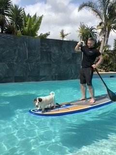 a man on a paddle board with a dog