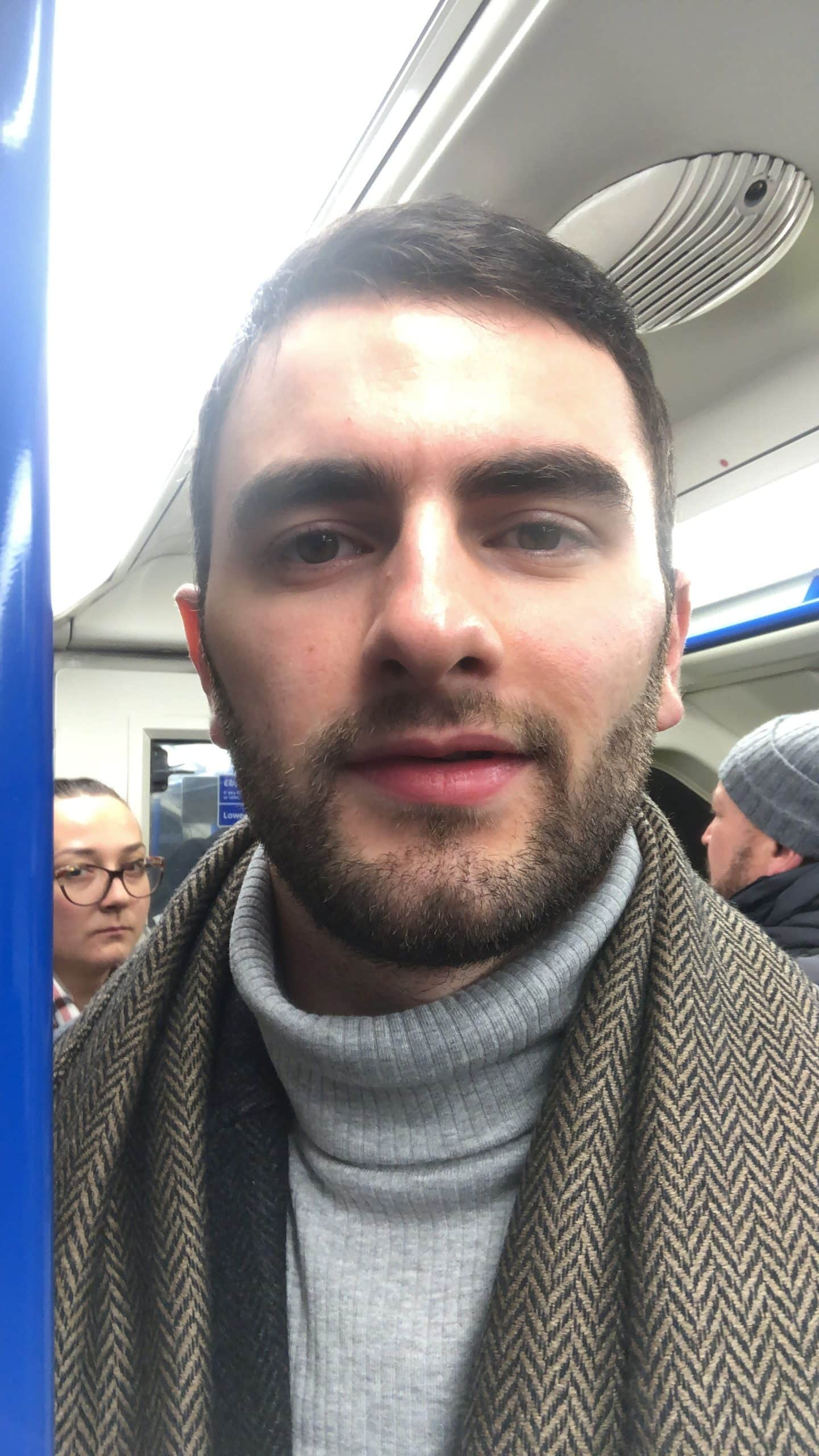 a man wearing a scarf standing on a train